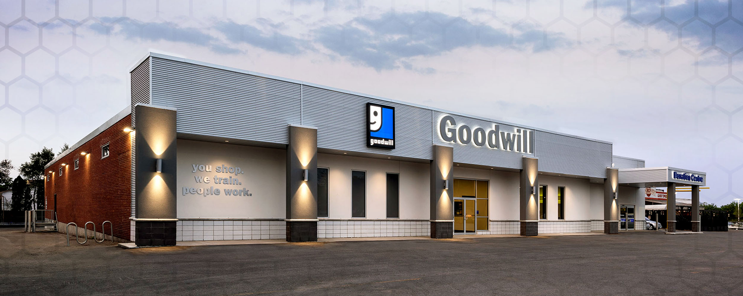 Commercial construction project, the Front of Goodwill store, London, Ontario which has 5 grey columns with lights, white exterior walls and the Goodwill Sign above the front door. There is a drive through area at the side of the building for donations to be dropped off.