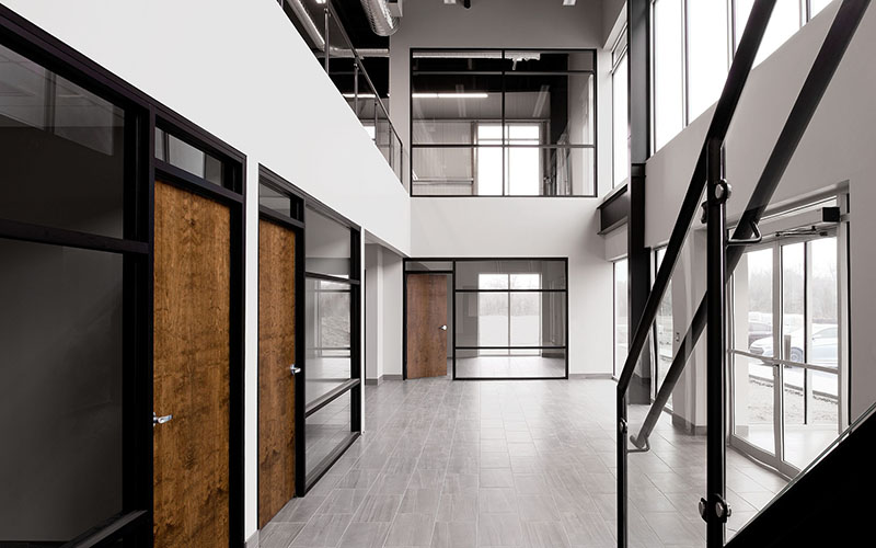 Cole Munro, Fish processing facility, the inside office area, 2 stories tall, with lots of windows, offices have wood doors and glass walls. Large area lit by natural outside light and open staircase to the second floor.
