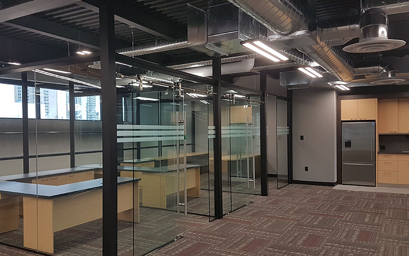 Roundhouse, interior office with floor to ceiling glass walls separating each desk area in this historic building with contempary modern elements.
