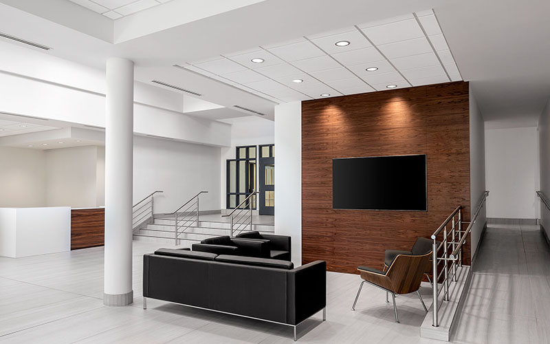 Starlim expansion, interior photo of the front lobby area with a black couch and chair and a TV on a brown wood lined wall with white walls and floors around it.