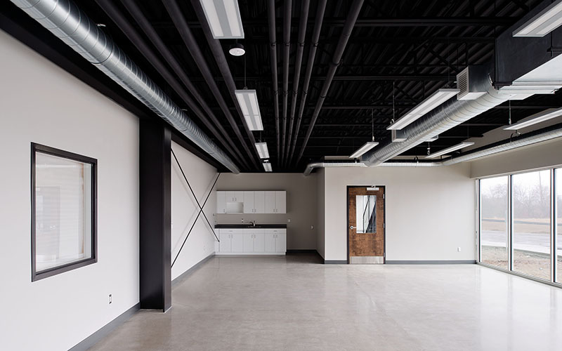 Cole Munro, Fish processing facility, showing the interior of office space with dark black ceilings and white cabinets on the far wall with a door on one wall as well.