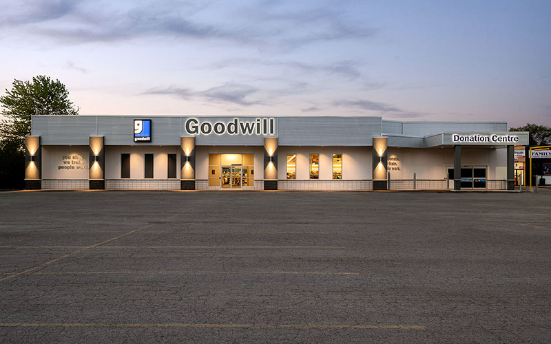 Commercial construction project, the front of Goodwill Store, London, Ontario showing the whole building, 5 grey columns spaced along the front with lights turned on, the Goodwill sign above the front in the center on a light blue background with the logo beside it.