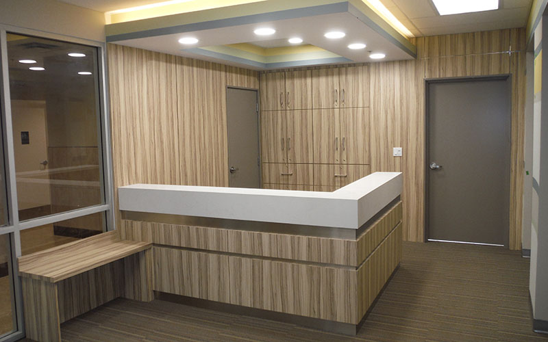 Nixon Medical, Reception area with desk and wood paneling on wall.
