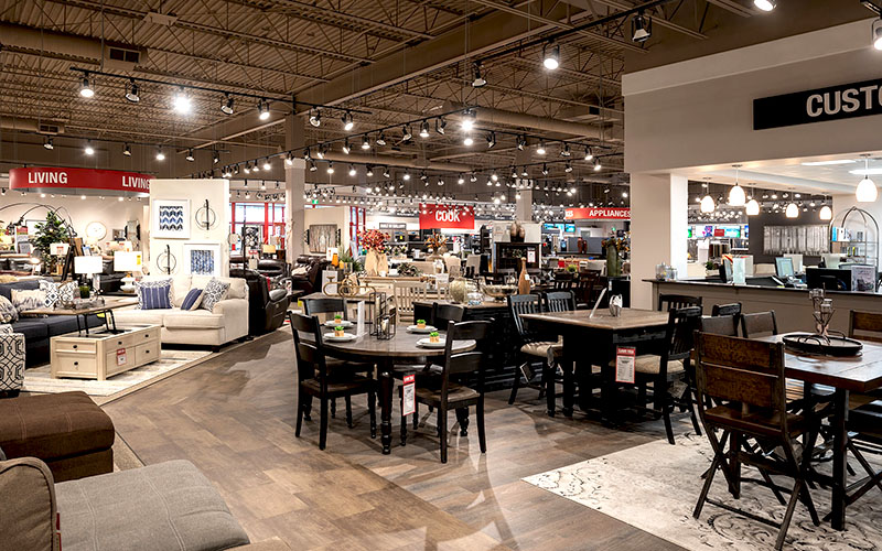 Inside of Teppermans, commercial renovation construction project, open retail showroom with tables and chairs set up for people to look at.
