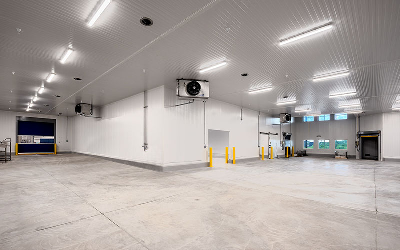 Cole Munro, Fish processing facility, the inside of a large empty area that has 2 storage areas, one for cold storage and white walls