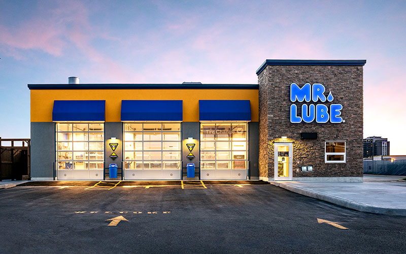 Sunset exterior photo of Mr. Lube showing the bay doors, and the front door with all the lights on.