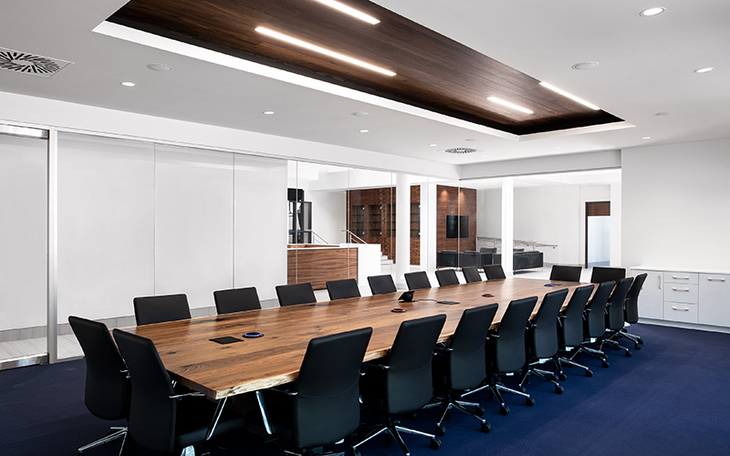 Starlim expansion,boardroom with a long wooden table and 18 black office chairs around it with white walls and recessed area in the ceiling with dark wood accents.