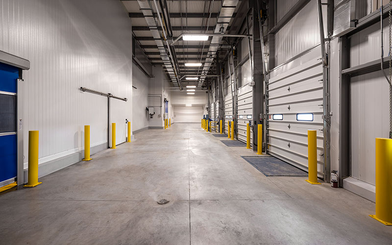 Cole Munro, Fish processing facility, their shipping area with large bay doors in an industrial building with white walls