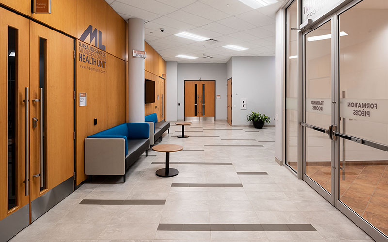 Middlesex London Health Unit, lobby area with double doors on each side and chairs along one wall