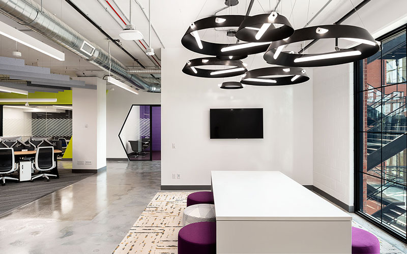 Carfax interior collaboration area with a white table, and white and purple stools.