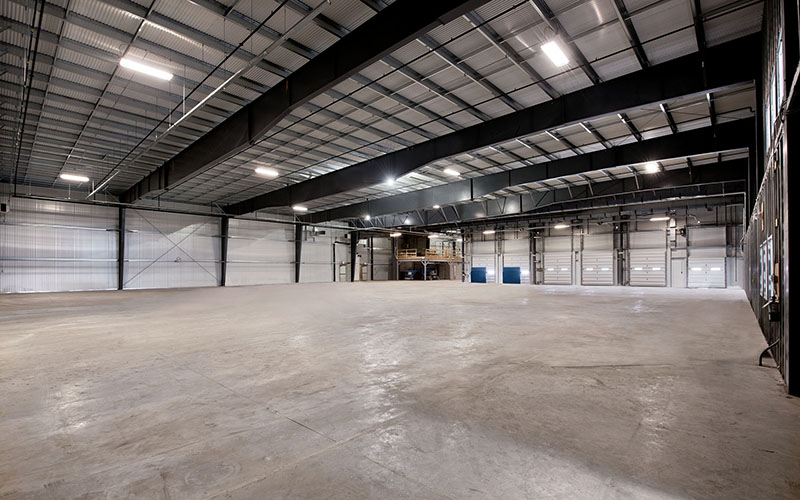Cole Munro, Fish processing facility, the inside of a large empty pre-engineered building area.