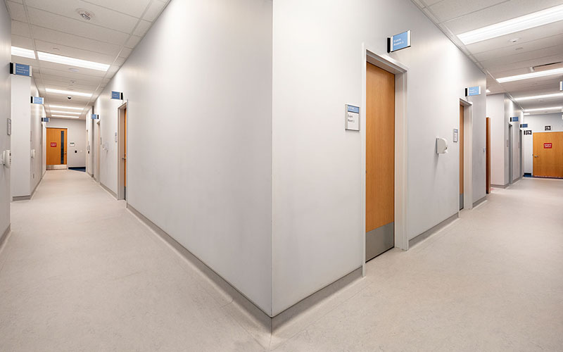 Middlesex London Health Unit, interior Photo of hallway with doors and white walls.