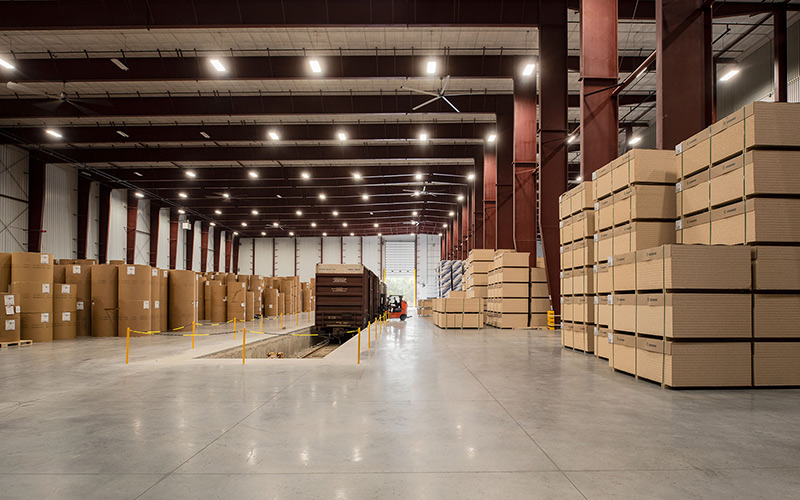 Logistics hub, interior open warehouse space with a opening in the concrete floor for train cars to be backed in a filled up with product that makes the train door level with the floor.