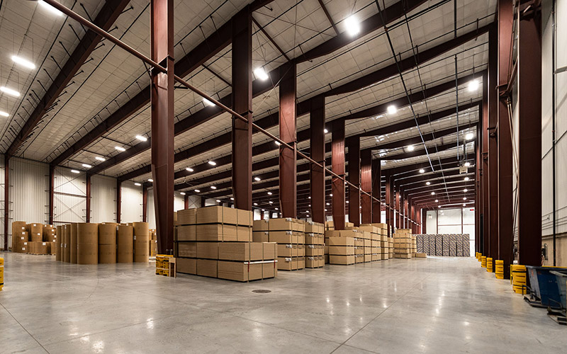 Logistics hub, interior of open warehouse space with brown metal floor to ceiling columns for support