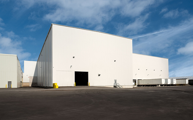Logistics Hub, white exterior building with a large bay door