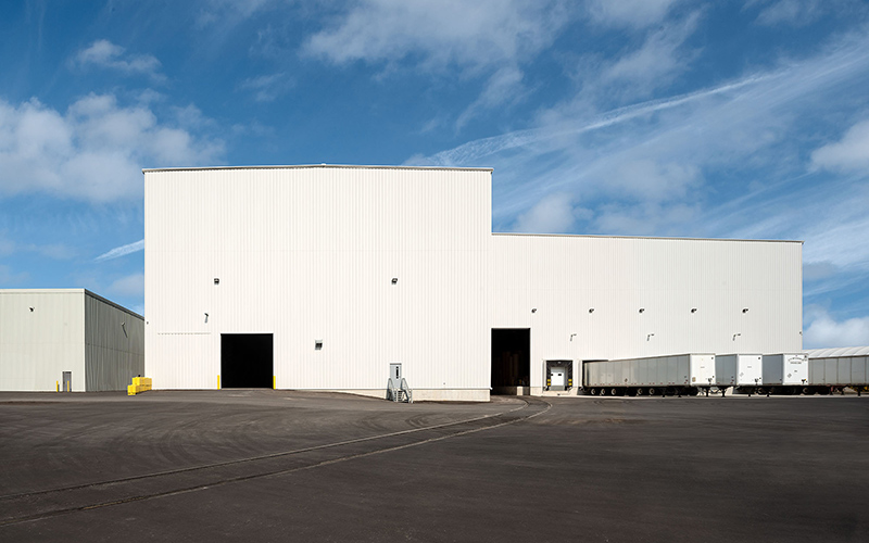 Logistics hub, white exterior of industrial building with docks for shipping trucks and man doors for people to walk through.