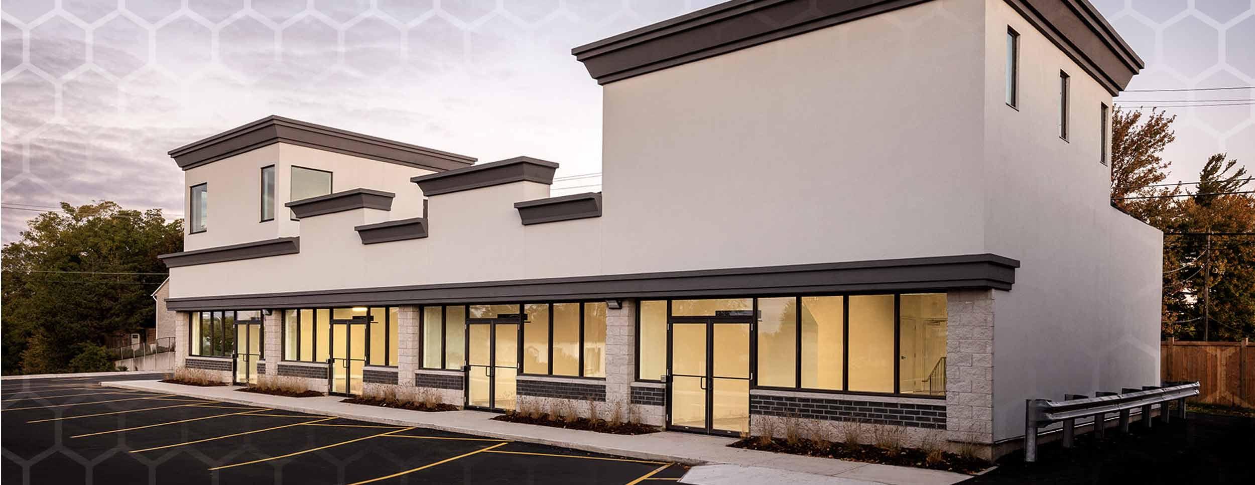801 Dundas Street Woodstock Retail office building that has light beige walls and dark brown trim. Glass windows all across the first floor.