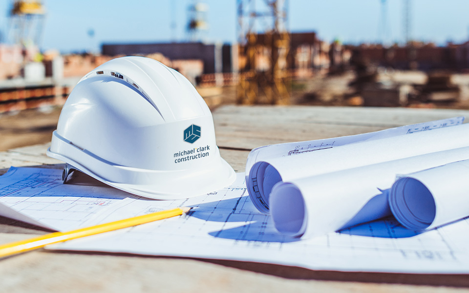 Construction Safety hat with michael + clark logo sitting on top of construction drawing.