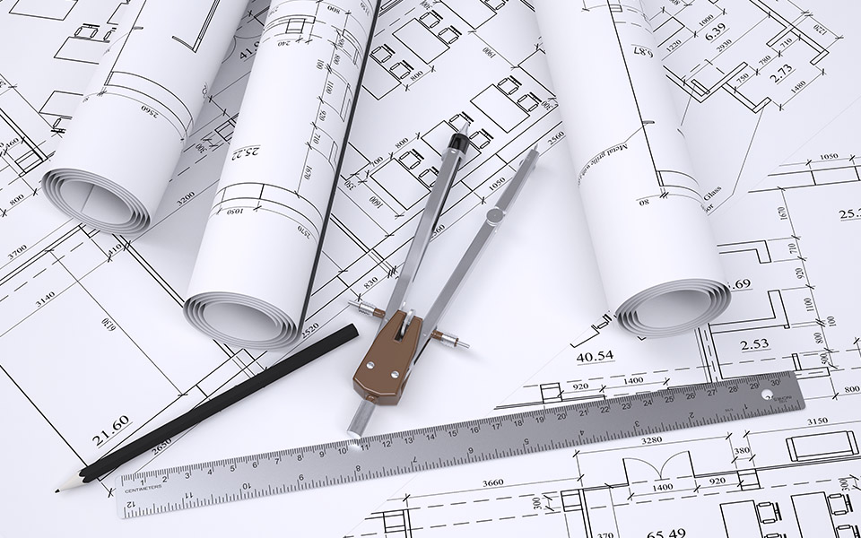 Engineering drawings for construction with a pencil, compass and ruler laying on top.
