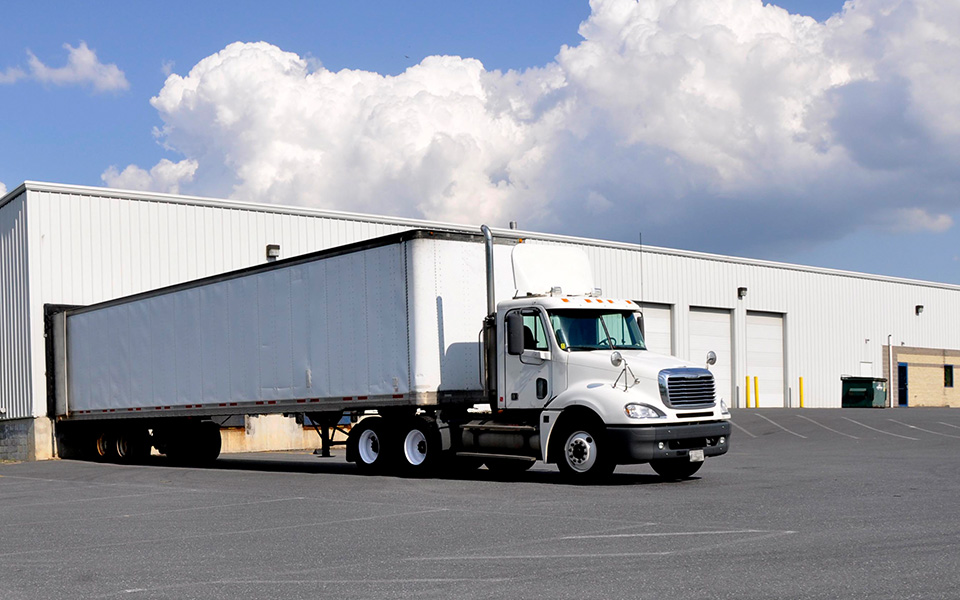 Exterior Photo of a Large White Warehouse with a large transport truck backed up to a loading dock.