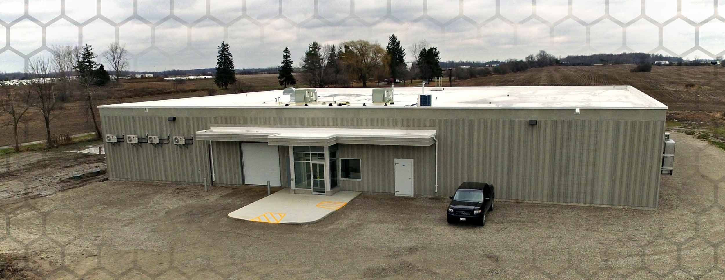 Exterior photo of Shogun Maitake, Mushroom growing facility. Grey concrete sides, no windows, other than around the front door, and a garage door to the side of the front door. White flat roof.