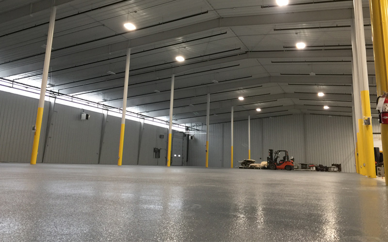 Interior Photo of an empty warehouse with white brick walls and grey concrete floors and metal posts painted yellow on the bottom half and white on the top. Forklift is in the background of the photo.