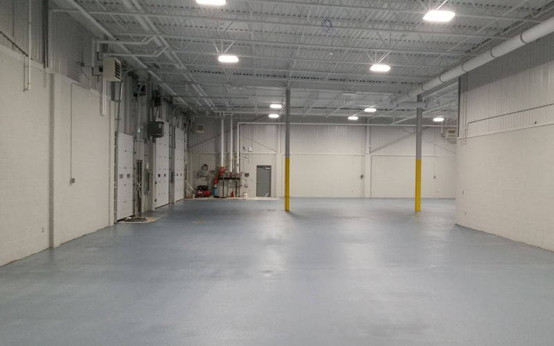 Interior Photo of an empty warehouse with white brick walls and grey concrete floors