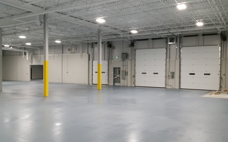 Interior Photo of an empty warehouse with white brick walls and grey concrete floors with 2 big white garage doors