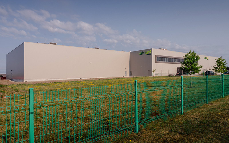 exterior view of Frulact building, beige metal siding and green metal fence surrounding property.