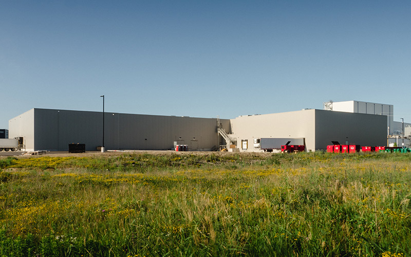 Exterior view of Frulact building, showing shipping docks, large transport truck trailer and large red metal square bins