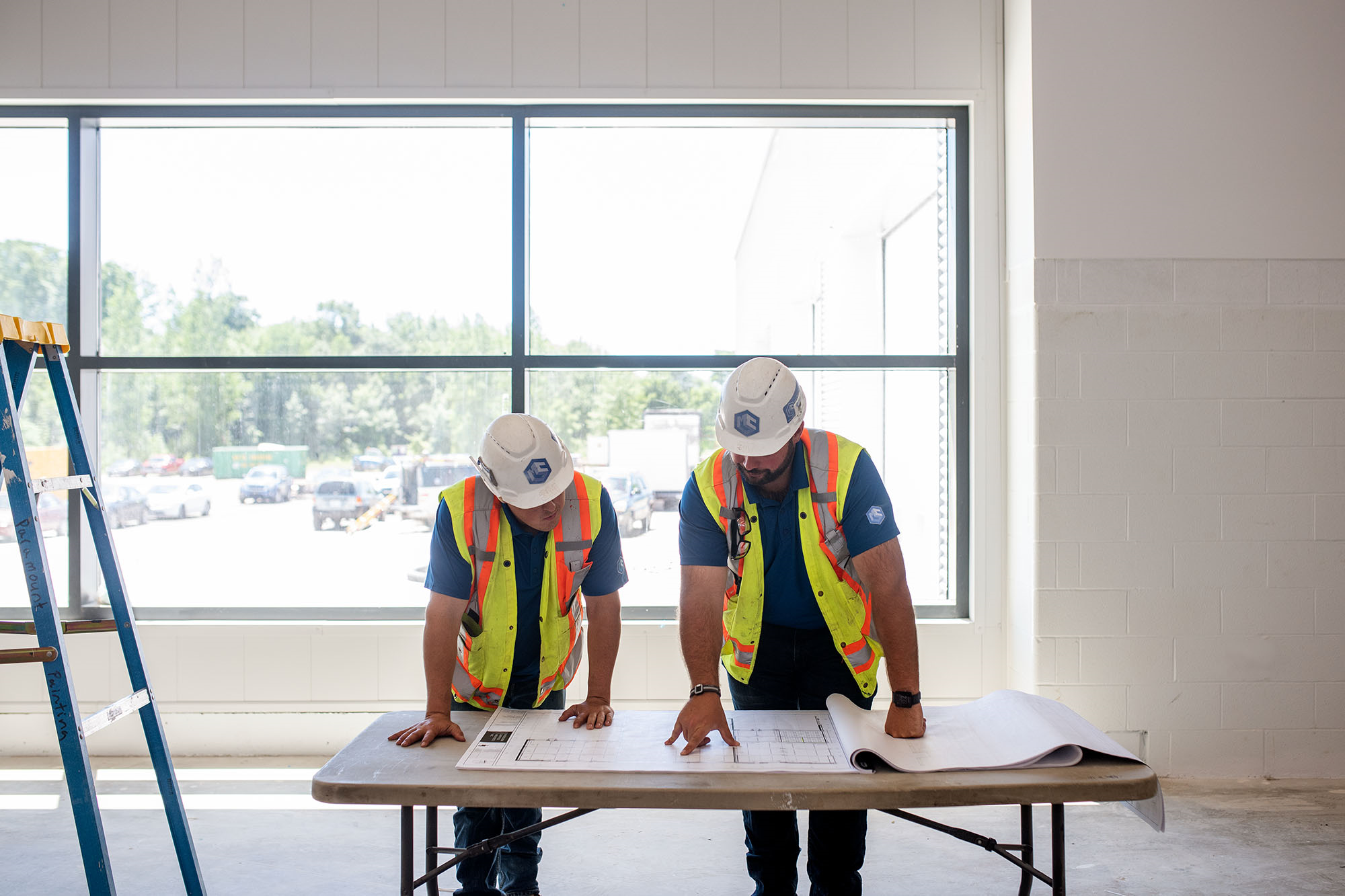two construction workers leaning forward on a table looking at a blueprint with a large window in the background.