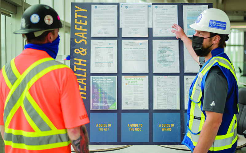 two construction workers discussion a health and safety board at a project site.