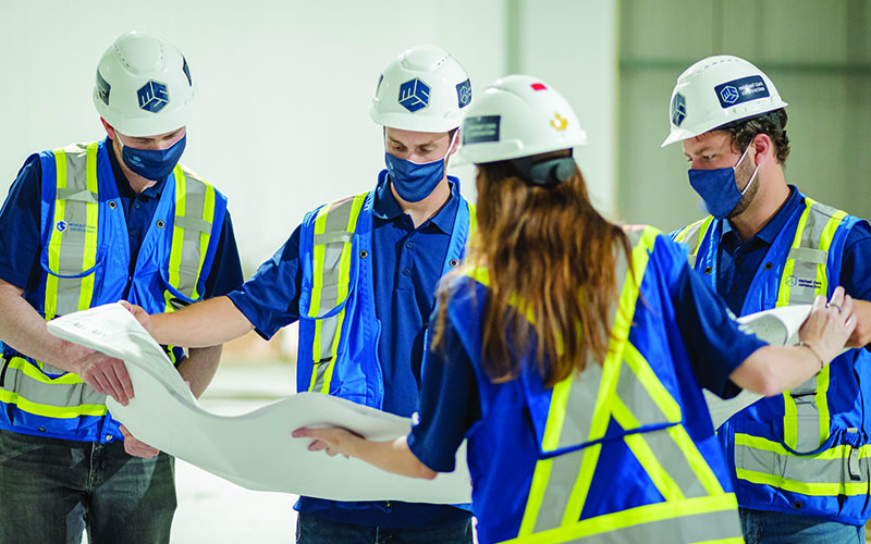 A group of construction workers holding a blue print and looking at it together.