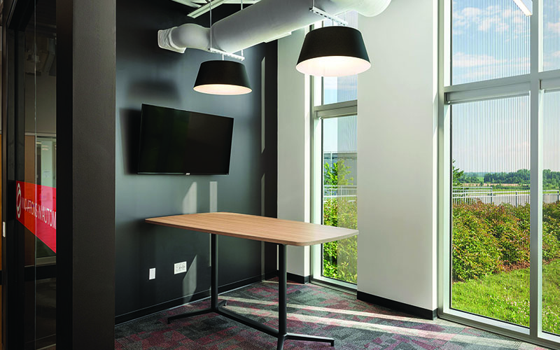 BOS Innovations at The Collider Western University Research Park, Photo of an interior office, black wall with TV hanging in the middle, board room table jutting straight out from the wall into the room and an adjacent wall with two floor to ceiling windows placed into the wall