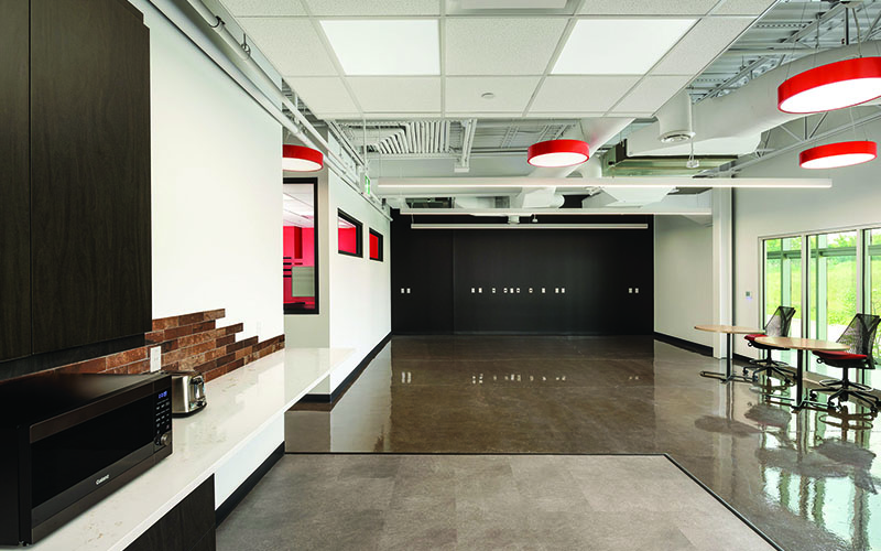 BOS Innovations at The Collider Western University Research Park, Photo of an interior space, open concept lunhc room, 2 white walls, large circular red pendelum lights hanging from the ceiling, glass windows on the left wall with chairs in front.