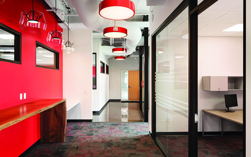 BOS Innovations at The Collider Western University Research Park, Photo of an interior hallway, Red wall on left side with partial long rectangular window three quarters of the way up, large red circular lights hanging from the ceiling in a row down the center of the hallway, floor to ceiling glass walls on the right