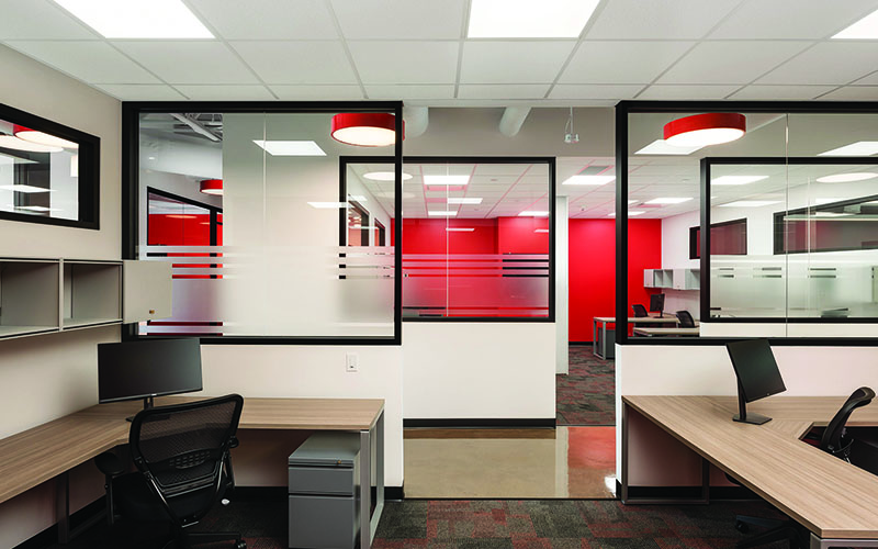 BOS Innovations at The Collider Western University Research Park, Photo of an interior space, showing the back of two desks, entrance in to the hallway in the middle and glass wall on the other side with red walls in the distance.