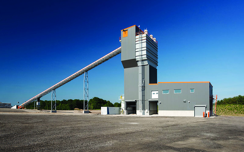 Photo of a concrete plant industrial facility, blue skies and it is in the middle of a open space. Grey L-shaped building standing towards the sky.