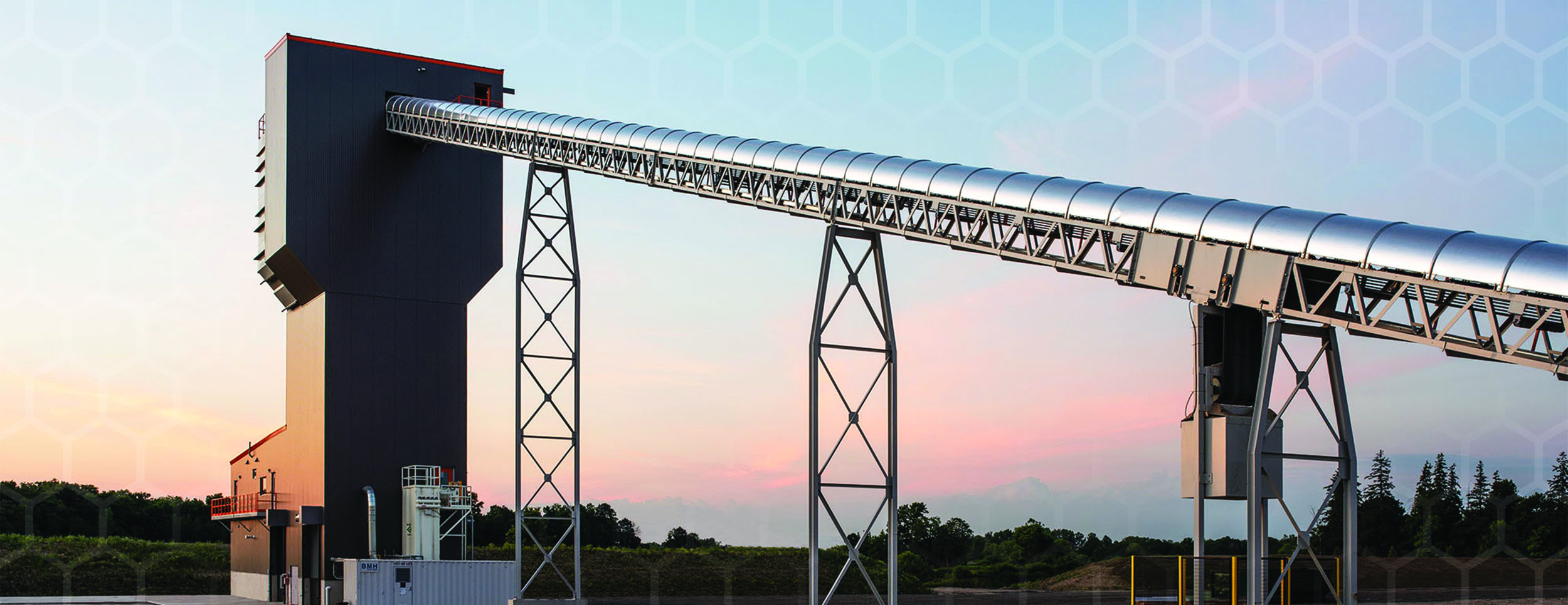 Evening Sunset Photo with a large steel round conveyor raising from the ground on a slant to the top of a tall building. The conveyor is supported by 2 steel tall supports at 2 intervels as it inclines.