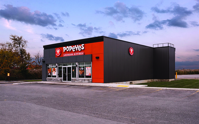 Side Rendering of Exterior Rendering of a Popeyes Restaurant at Sunset. Dark Grey brick with pops of Red along the top and down the right side of the front of the building. Dark grey for the side wall of the building.