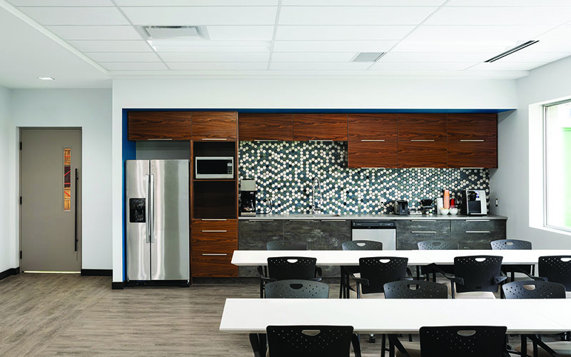 Interior Photo of Spark Power Lunchroom, In the distance there is a wall with dark wood cabinets, a stainless steel fridge and counter top, tables with chairs and window to the right side with multicolored brown grey flooring.