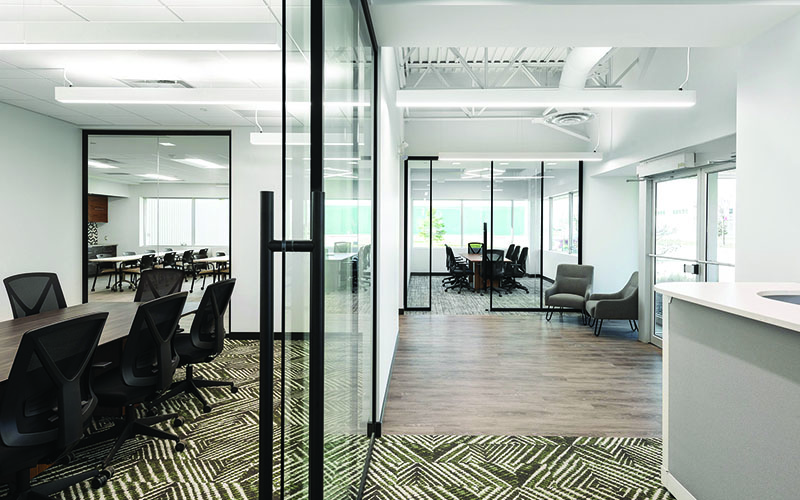 Interior Photo of Spark Power Office, Long hallway to the right side, and down the left is glass walls for a boardroom. hardwood flooring and multicolored grey and yellow carpet.