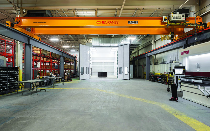 Interior Photo of Spark Power warehouse area with a large orange overhead crane in the center and concrete floor underneath.