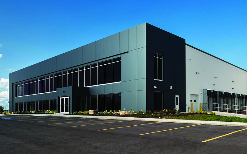 Cole Munro, St. Thomas, Fish processing facility, large industrial building that has windows along the front with dark grey building tiles around it and the rest of the building is white with parking spots out front.