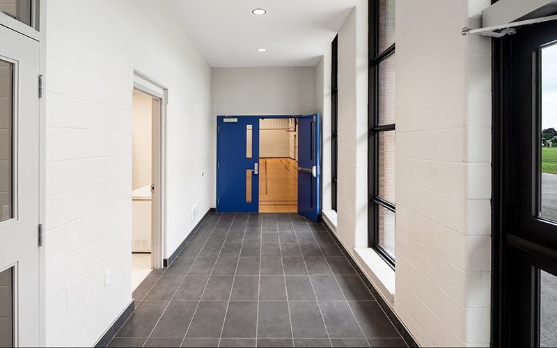 Covenant School, interior photo of a hallway leading to the gym in the distance with white cinder block walls and grey tiled flooring. Royal Blue doors flank the entrance to the gym.