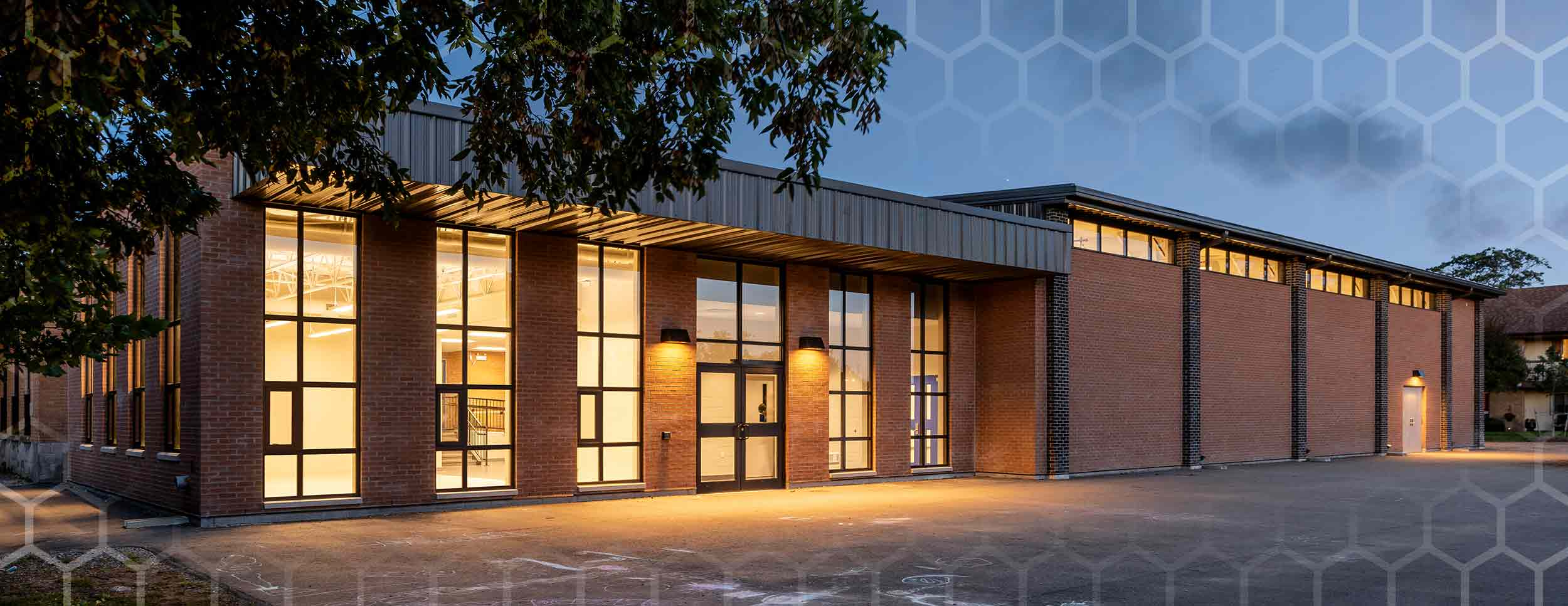 Covenant School, exterior evening photo showing front of the building with an interior room to the left lit up through the windows. Brown Brick facade and black window outlines