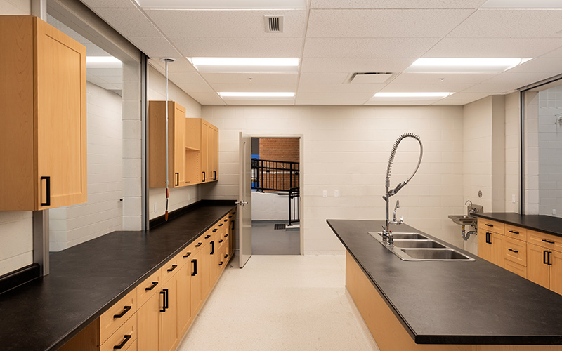 Covenant School, interior photo of kitchen with light oak cabines along the left and right, black laminate countertop with black drawer handles and black door handles. In the middle of a room is an island of light oak with black laminate counter top, triple sink in the center and a hand held extendible faucet.