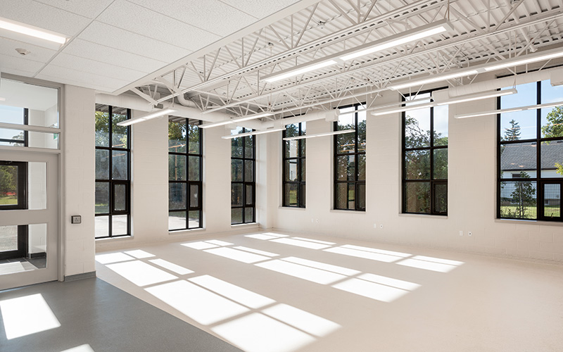 Covenant School, photo of an interior room with large windows spaced out around the room, large front doors leading into the room from the left. White walls, flooring and ceiling.