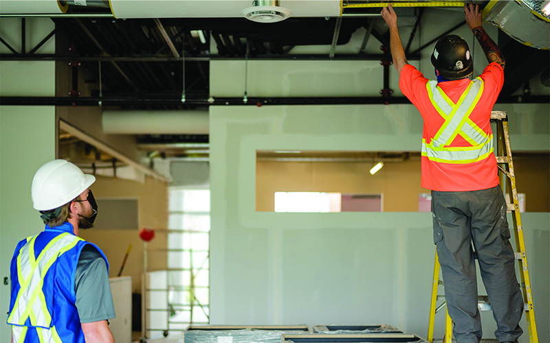 Photo of two construction people in a room, both with backs to the viewer, one standing on a ladder holding an extended measuring tape up to the ceiling.