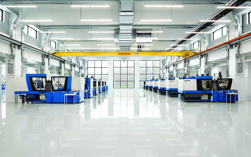 Starlim production room, open concept, white floor, walls and ceilings with automated machines down the left and right. Full wall of 12 windows in a rectangle pattern.